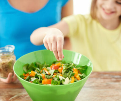 food, healthy eating, family and people concept - close up of happy girl and mother cooking salad fo
