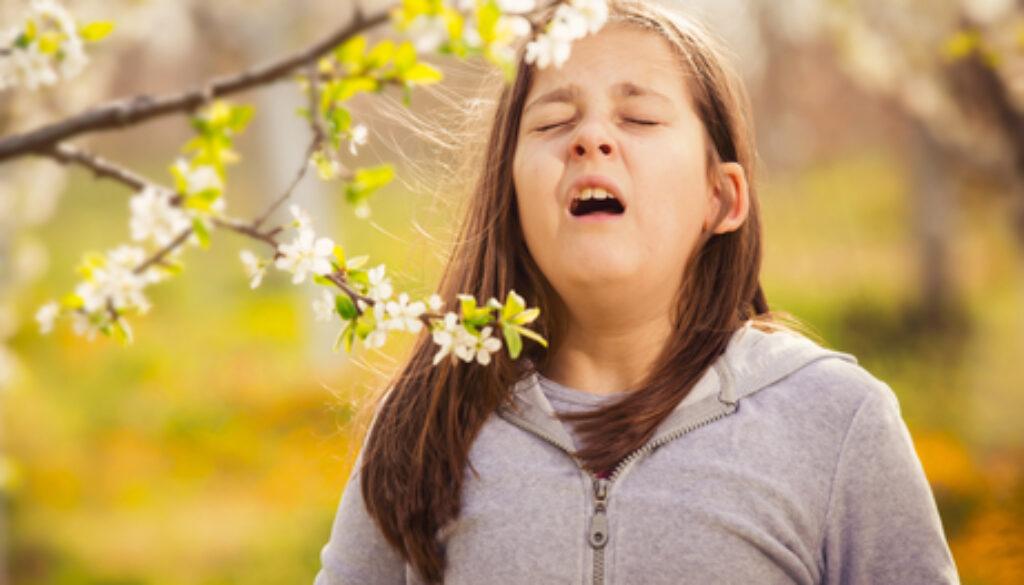 Girl having allergy outdoor. The girl sneezes. Selective focus